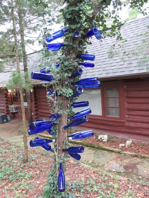 Bottle tree with blue bottles hanging on it Cabins in the background