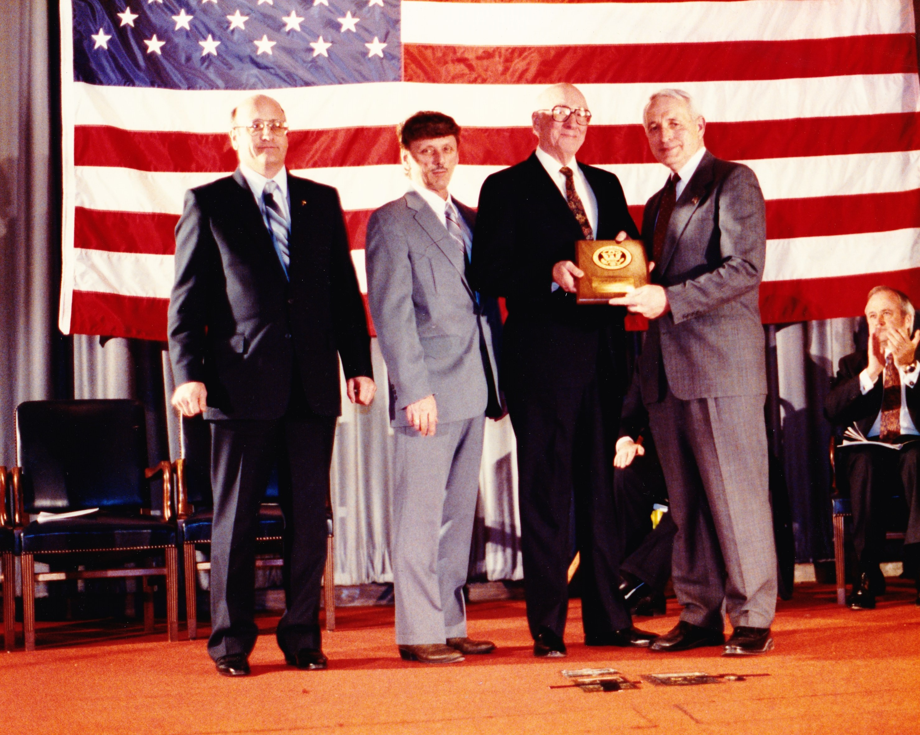 three men receiving an award from another man with the american flag hanging behind them