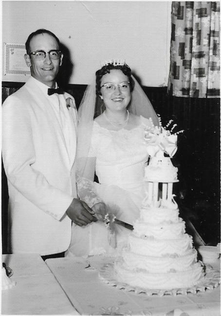 man and woman standing at a wedding cake dressed for a wedding