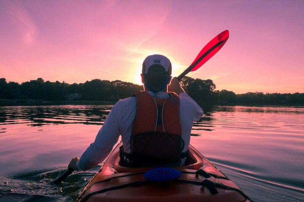 man kayaking into the sunset