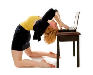 Business women bending over backwards at a computer