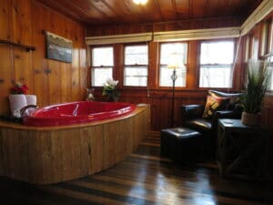 cabin with hardwood floors and red jetted tub
