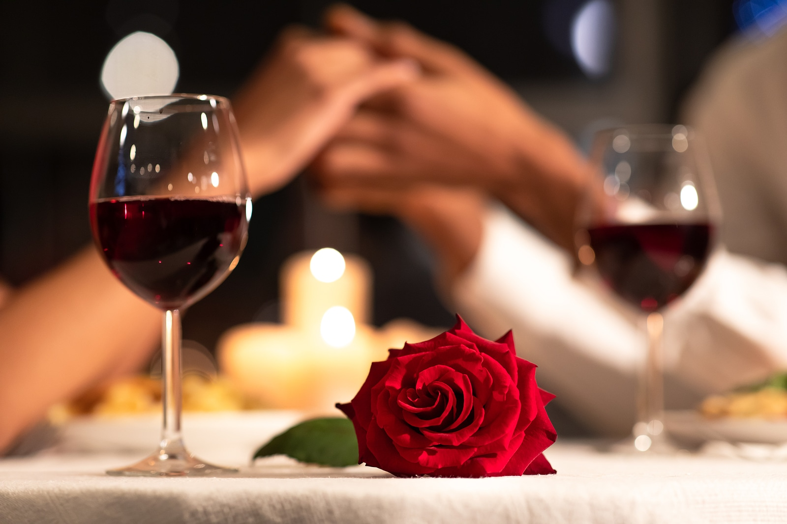 two wine glasses with a rose in the middle and two people holding hands