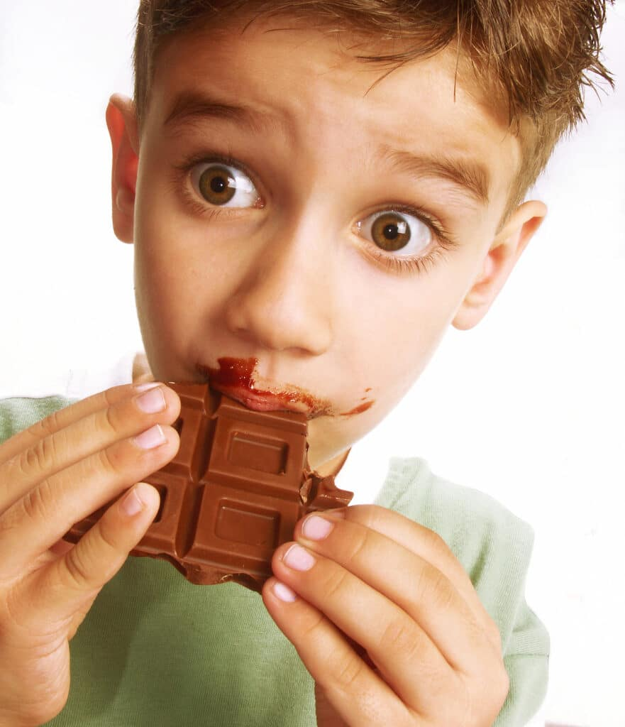 Boy enjoying eating chocolate bar with chocolate all over face