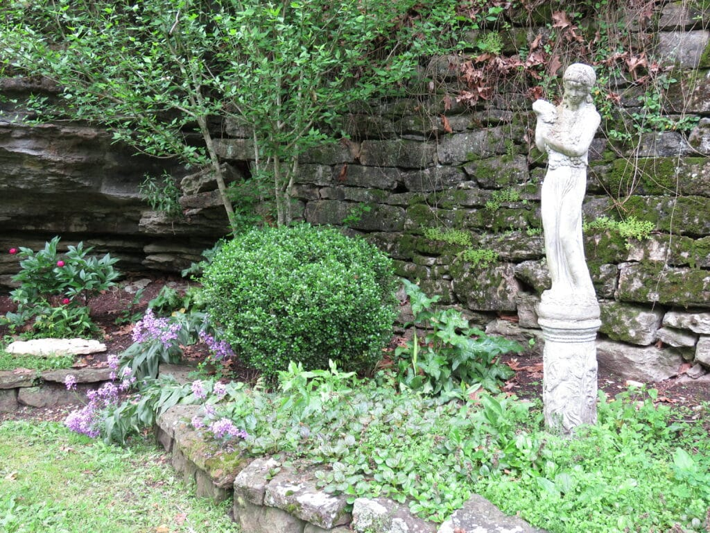 Outside Laundry spring white statue surrounded by greenery and flowers