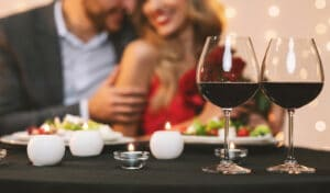 Couple enjoying romantic dinner with red wine and salad