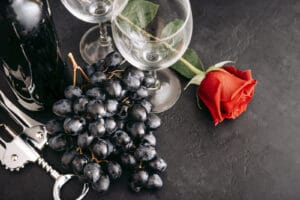 Purple grapes sitting between two wine empty wine glasses and one long stem red rose sitting next to the wine glasses