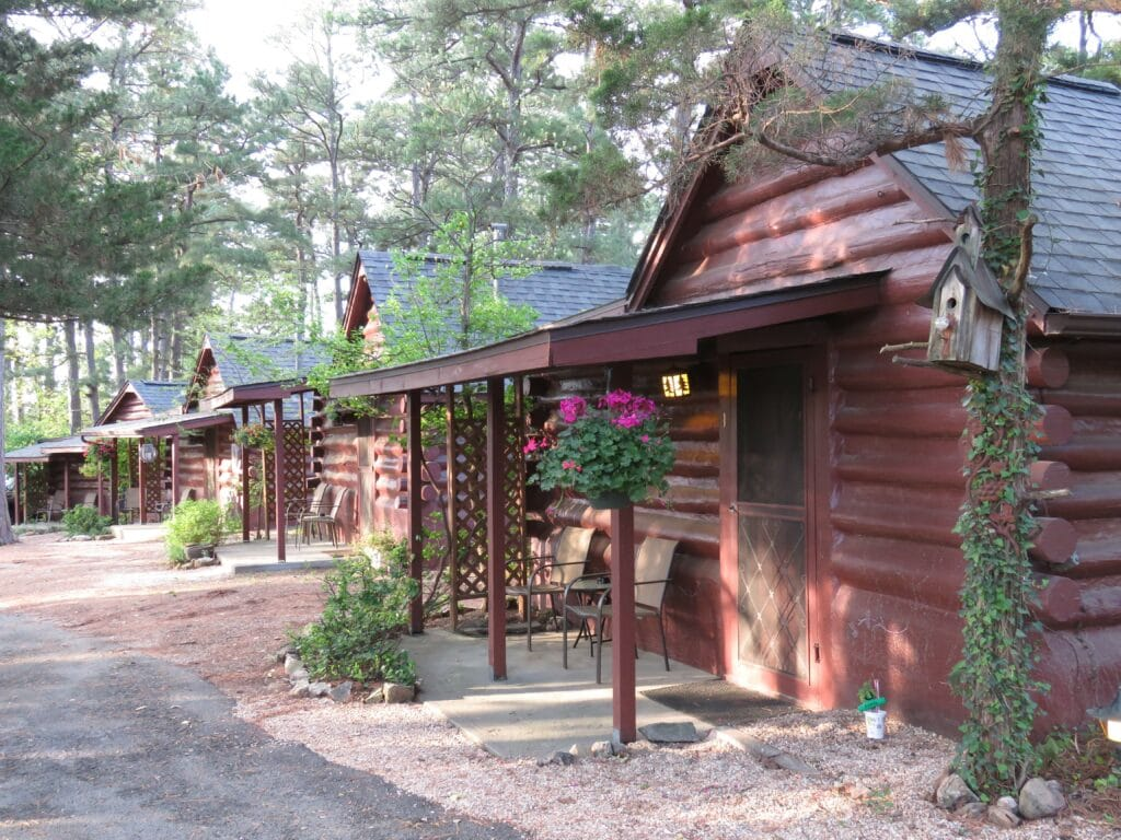 historic cabin situated all in row with plants hanging by the doors