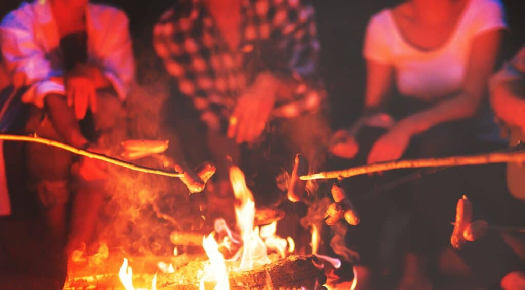 group of friends sitting around a campfire at night roasting marshmallows on sticks