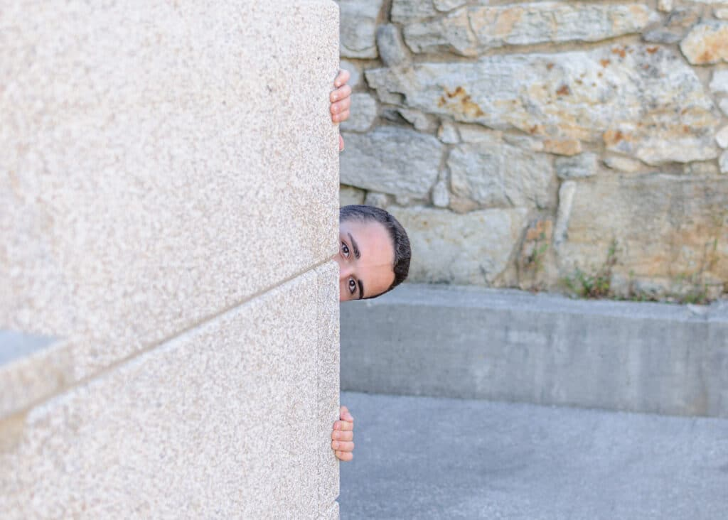 man peeking around the corner of a building with only his eyes fingers showing