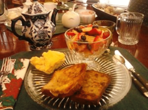 breakfast at a beautiful table showing a plate with french toast, scrambled eggs, and a dish with fruit
