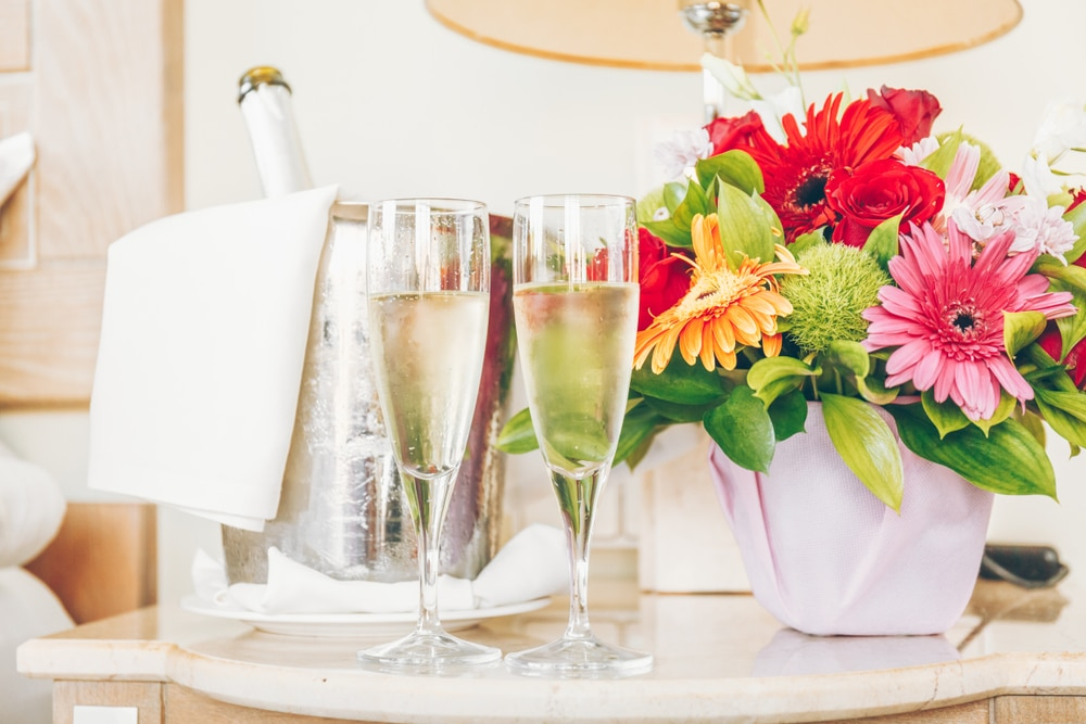 two champagne flutes filled with champagne sitting by a bouquet of colorful daisies